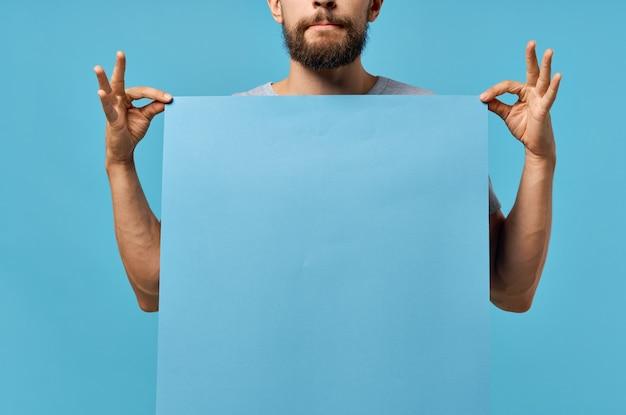 Bärtiger mann, der einen isolierten hintergrund mit mockup-posterrabatt hält. foto in hoher qualität