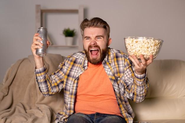 Bärtiger mann, der film- oder sportspiele im fernsehen sieht und popcorn im haus bei der nachtkino-meisterschaft isst und