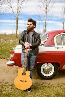 Bärtiger mann, der gitarre draußen nahe retroauto spielt