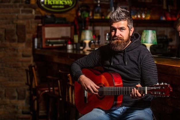 Bärtiger mann, der gitarre spielt und eine akustikgitarre in seinen händen hält
