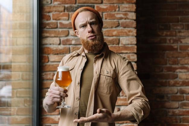 Bärtiger mann, der glas bier hält und alkohol in der kneipe trinkt