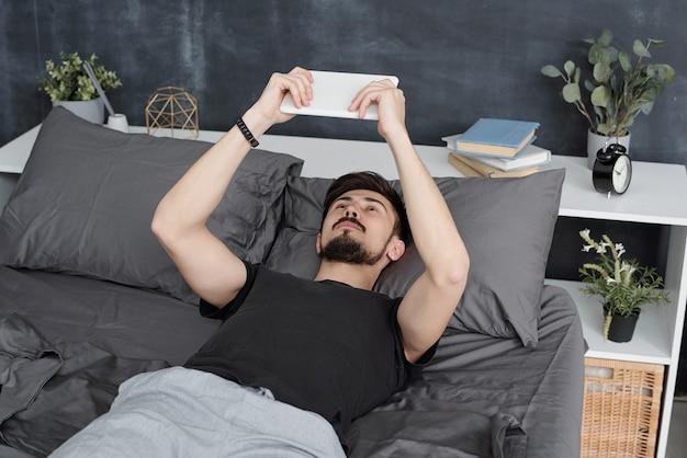 Bärtiger mann, der im bett liegt und tablette benutzt, während er zeit zu hause während der quarantäne verbringt