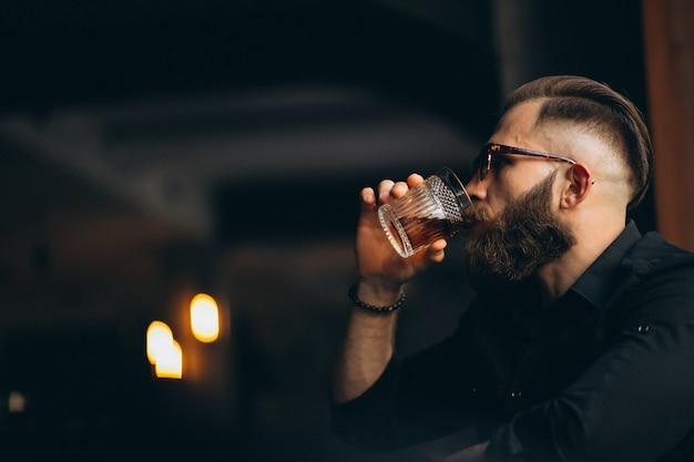 Bärtiger mann, der in einer bar trinkt