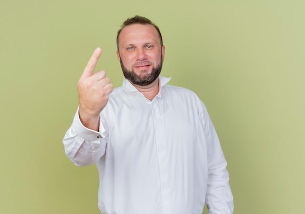 Bärtiger mann, der lächelndes weißes hemd zeigt zeigefinger oder nummer eins steht über heller wand