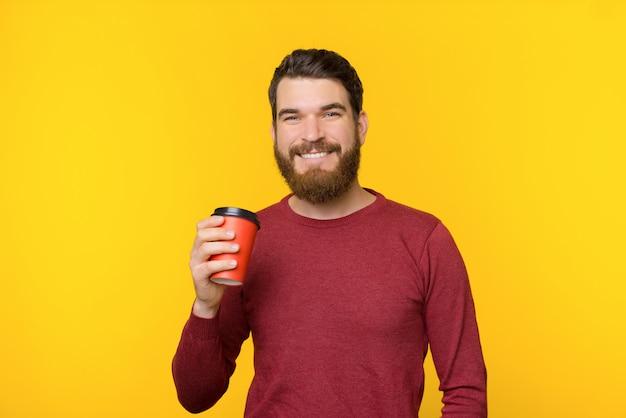 Bärtiger mann, der lächelt und eine tasse heißes getränk auf gelbem hintergrund hält.
