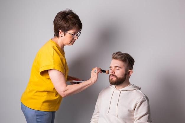 Bärtiger mann, der make-up-frau visagist bekommt, arbeitet mit pinsel