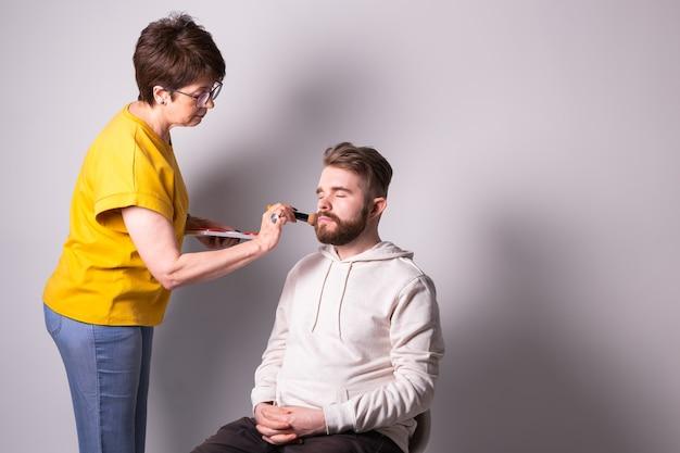 Bärtiger mann, der make-up-frau visagist bekommt, arbeitet mit pinselexemplar
