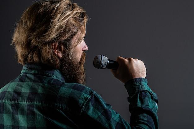 Bärtiger mann, der mit mikrofon singt