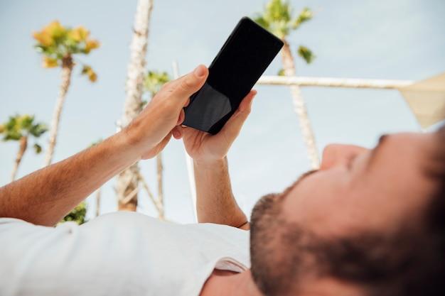 Bärtiger mann, der modernes telefon anhält