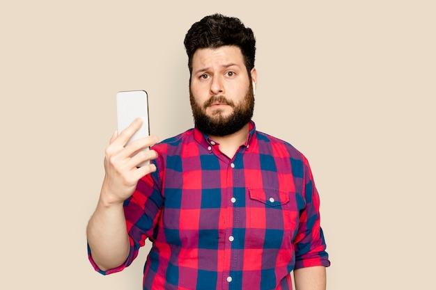 Bärtiger mann, der musik mit digitalem smartphone-gerät streamt