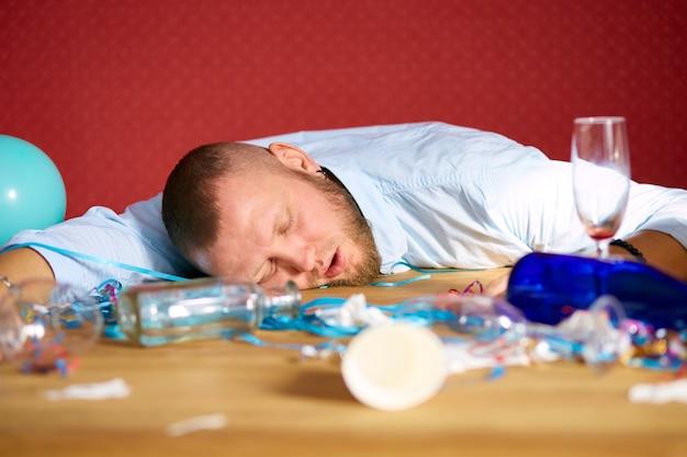 Bärtiger mann, der nach dem junggesellenabschied am tisch in einem unordentlichen zimmer schläft