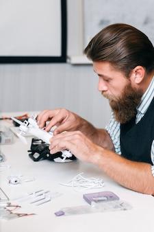 Bärtiger mann, der neuen quadrocopter untersucht. drohnen kürzlich getestet. elektronik, technologie, hobby, aeromodelling-konzept