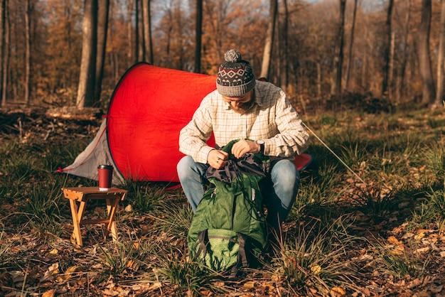 Bärtiger mann, der rucksack auf campingplatz auspackt