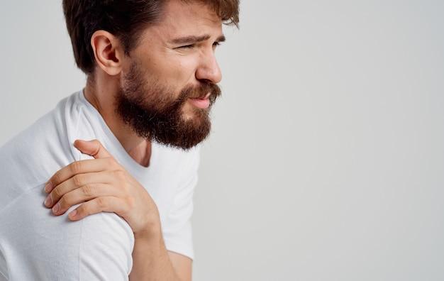 Bärtiger mann, der schulter mit handschmerz berührt, disman im weißen t-shirt, das unter schmerzen leidet