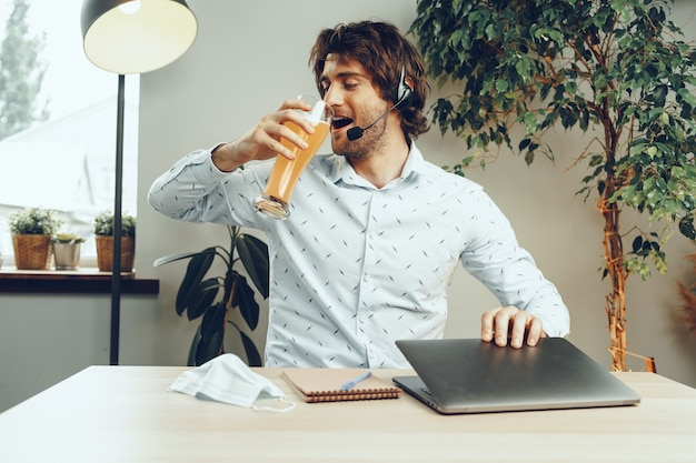 Bärtiger mann, der seinen laptop benutzt, während er ein glas bier trinkt