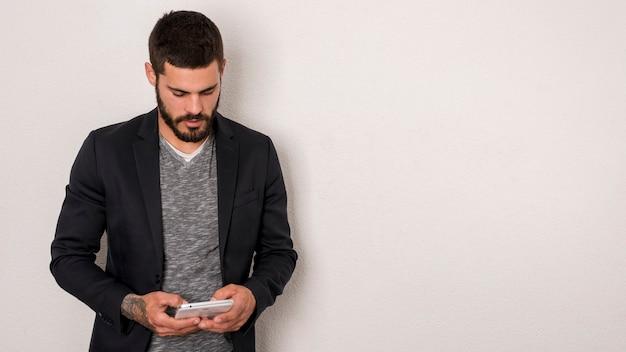 Bärtiger mann, der smartphone auf weißem hintergrund verwendet