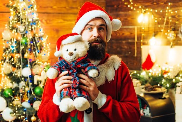 Bärtiger mann, der spaß nahe weihnachtsbaum drinnen hat