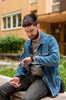 Bärtiger mann, der uhren beim halten des smartphone betrachtet