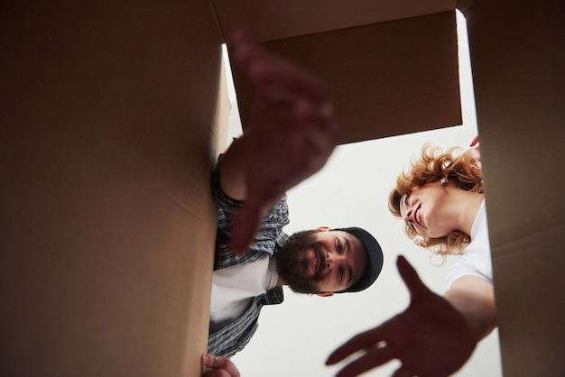 Bärtiger mann, der versucht, den gegenstand aus einer kiste zu erreichen. glückliches paar zusammen in ihrem neuen haus. konzeption des umzugs