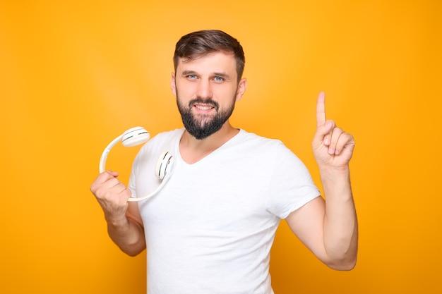 Bärtiger mann, der weiße musikkopfhörer in der hand hält und daumen nach oben zeigt.