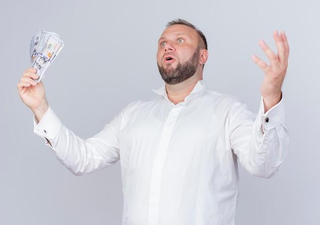 Bärtiger mann, der weißes hemd hält, das bargeld hält, das beiseite schaut und hand überrascht und sehr besorgt über weißer wand steht