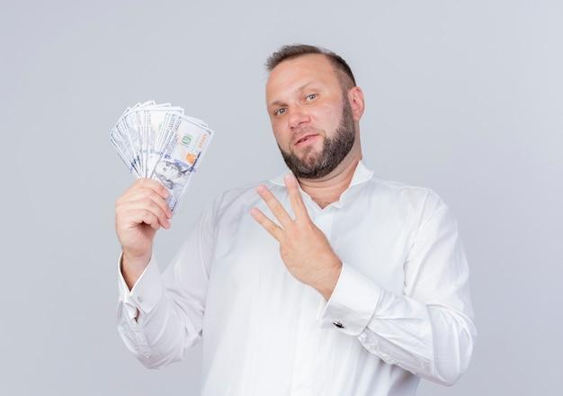Bärtiger mann, der weißes hemd hält, das bargeld zeigt und mit den fingern nummer drei zeigt, die zuversichtlich lächelnd über weißer wand stehen