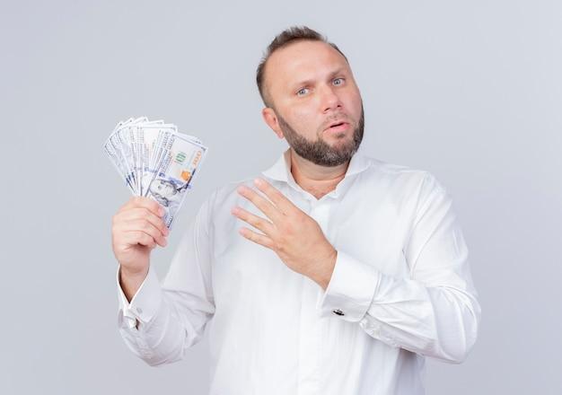 Bärtiger mann, der weißes hemd hält, das bargeld zeigt und mit den fingern nummer vier zeigt, die überrascht über weißer wand stehen