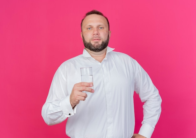 Bärtiger mann, der weißes hemd hält, das glas wasser mit ernstem gesicht hält, das über rosa wand steht
