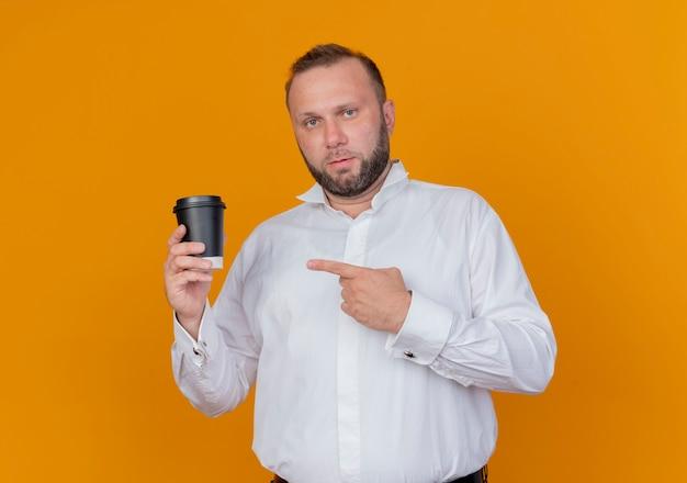Bärtiger mann, der weißes hemd hält, das kaffeetasse hält, die mit index-figner darauf lächelt und über orange wand steht