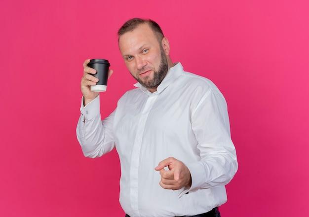 Bärtiger mann, der weißes hemd hält, das kaffeetasse pointign mit lächelndem zeigefinger hält, der über rosa wand steht