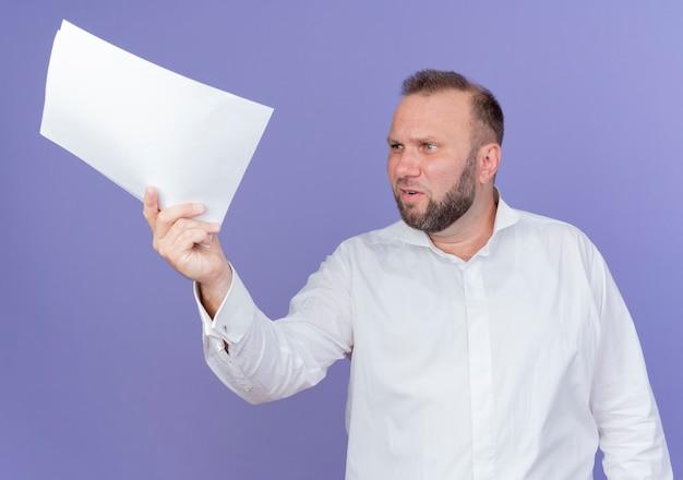 Bärtiger mann, der weißes hemd hält, das leeres blatt papier hält, das beiseite schaut, unzufrieden zu stehen, das über blaue wand steht