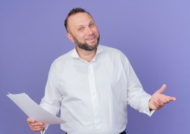 Bärtiger mann, der weißes hemd hält, das leeres blatt papier hält, das lächelnd über blauer wand steht