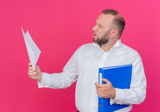 Bärtiger mann, der weißes hemd hält, das ordner und leere papierblätter hält, die beiseite über rosa verwirrt schauen