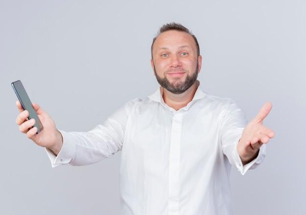 Bärtiger mann, der weißes hemd hält, das smartphone hält, das begrüßungsgeste mit handlächeln über weißer wand macht