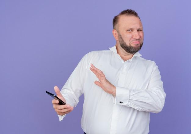 Bärtiger mann, der weißes hemd hält, das smartphone hält verteidigungsverteidigungsgeste mit hand, die mit angewidertem ausdruck steht, der über blaue wand steht