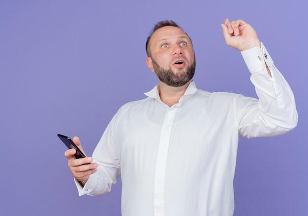 Bärtiger mann, der weißes hemd hält, das smartphone schaut, das überrascht zeigt zeigefinger, der neue idee hat, die über blaue wand steht