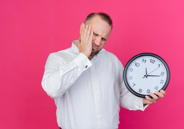 Bärtiger mann, der weißes hemd hält, das wanduhr hält und verwirrt steht über rosa wand