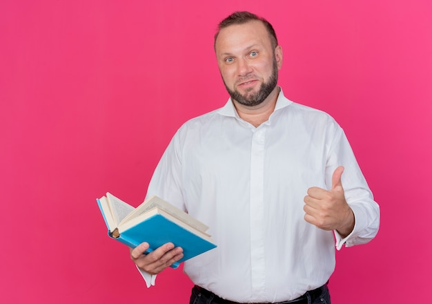 Bärtiger mann, der weißes hemd hält offenes buch lächelnd zeigt daumen hoch stehend über rosa wand