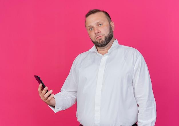 Bärtiger mann, der weißes hemd hält smartphone mit ernstem gesicht, das über rosa wand steht