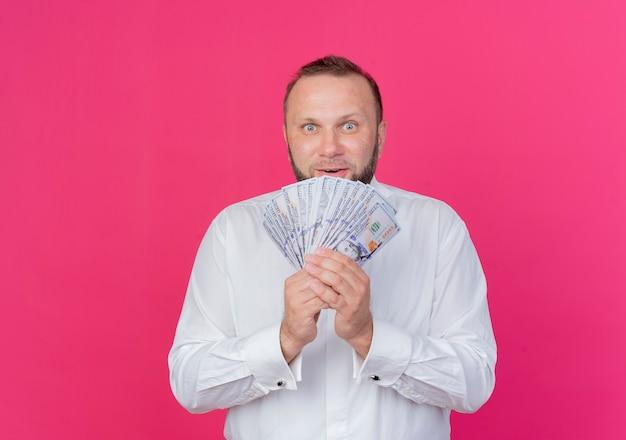 Bärtiger mann, der weißes hemd trägt, das bargeld sieht, das überrascht steht über rosa wand steht
