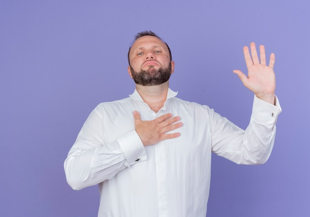 Bärtiger mann, der weißes hemd trägt, das einen eid mit dem selbstbewussten ausdruck leistet, der über der blauen wand steht