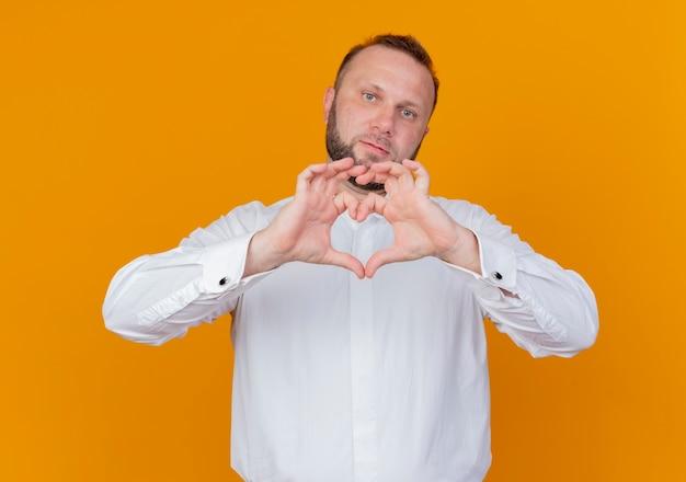 Bärtiger mann, der weißes hemd trägt, das herzgeste lächelnd macht, das über orange wand steht
