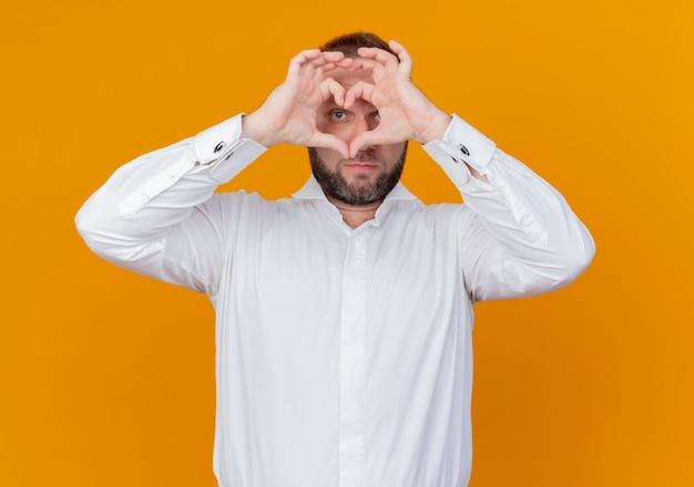 Bärtiger mann, der weißes hemd trägt, das herzgeste mit den fingern macht, die durch finger schauen, die über orange wand stehen