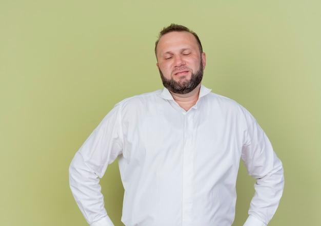 Bärtiger mann, der weißes hemd trägt, das mit armen an der hüfte, die über heller wand steht, unzufrieden aussieht