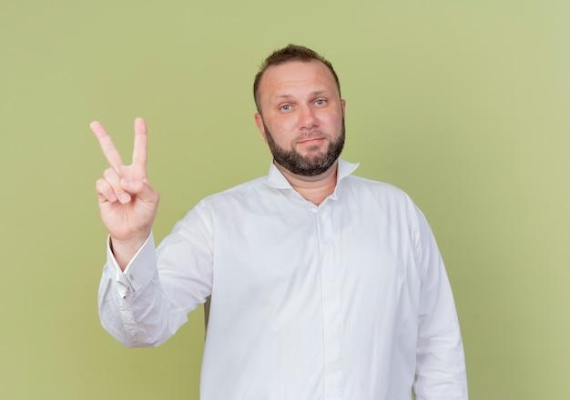 Bärtiger mann, der weißes hemd trägt, das mit den fingern nummer zwei zeigt und zeigt, die mit ernstem gesicht schauen, das über heller wand steht