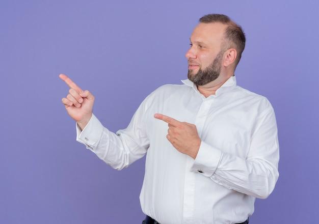 Bärtiger mann, der weißes hemd trägt, das mit lächeln zeigt, zeigt mit zeigefingern zur seite, die über blauer wand steht