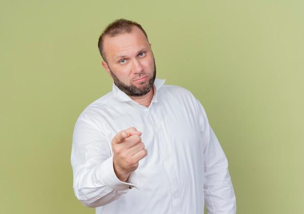 Bärtiger mann, der weißes hemd trägt, das mit zeigefinger zeigt, der unzufrieden steht, über heller wand stehend