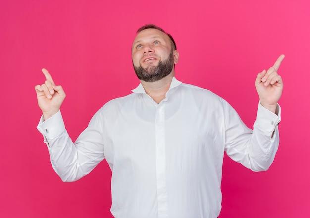 Bärtiger mann, der weißes hemd trägt, das mit zeigefingern zeigt, die glücklich und positiv lächelnd über rosa wand lächeln