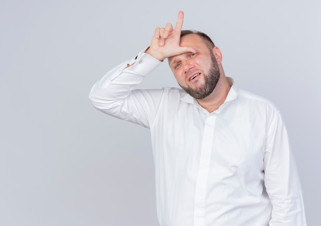 Bärtiger mann, der weißes hemd trägt, das verlierergeste mit den fingern tut, die müde und gelangweilt über weißer wand stehen