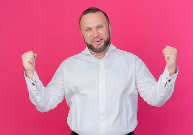 Bärtiger mann, der weißes hemd trägt geballte fäuste glücklich und aufgeregt freut sich über seinen erfolg, der über rosa wand steht